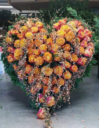 Herzförmiges Trauergesteck mit Rosen und Ginster-Zweigen