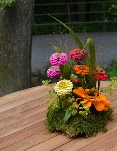 Blütenarrangement auf Moos